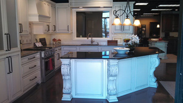 white acanthus leaf corbel on white kitchen island with black marble counter phoenix cabinet cures